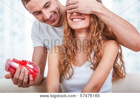 young man gives her a heart shaped gift
