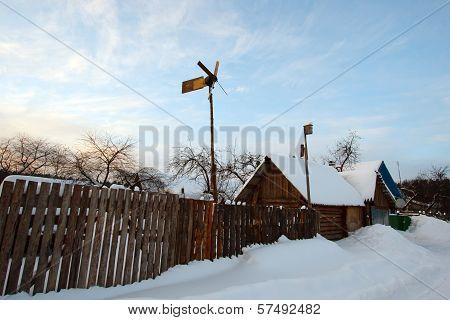 Winter rural landscape with village and vane