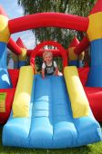 stock photo of inflatable slide  - child in bouncy castle - JPG