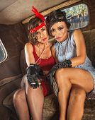 stock photo of gangster necklace  - Pair of pretty 1920s flapper women in car - JPG