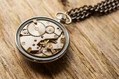 Pocket watch mechanism on wood background