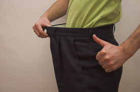 stock photo of bulging belly  - Close up on slimmed down male waistline wearing old trousers and thumbs up to demonstrate pleasure at weight loss - JPG
