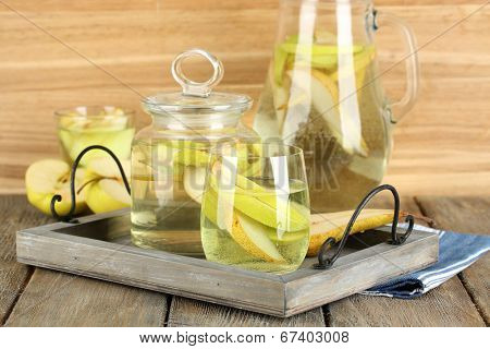 Sangria drink in glass and jar on wooden background
