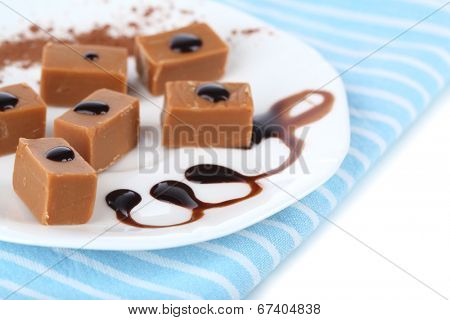 Many toffee on plate on napkin isolated on white