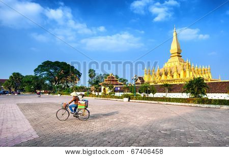 VIENTIANE, LAOS - 11 DEC,2013: Unidentified local woman on the bicycle on the square near golden pagoda wat Phra That Luang in Vientiane. Popular travel destination