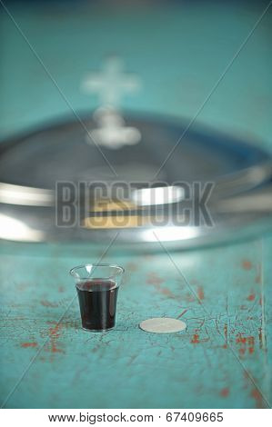 Cup of wine and wafer on vintage table - focus on foreground with shallow depth of field