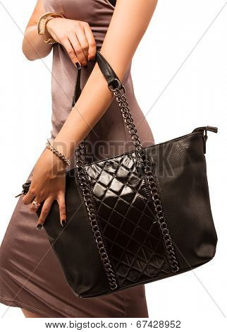 Closeup of woman with quilted fashion leather black bag with chains. Isolated on the white studio background.