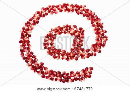 At symbol made from pomegranate seeds