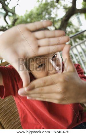Niño mirando a través de las manos