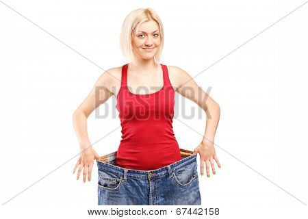 Woman standing in a pair of oversized jeans isolated against white background