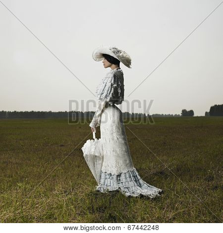 Slender woman in vintage dress for promenade