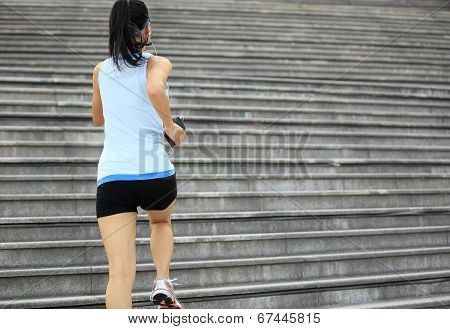 Runner athlete running on stairs. listening to music in headphones from smart phone mp3 player woman