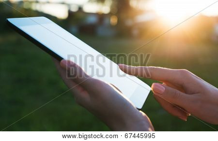 Close up of a womman using mobile tablet pc outdoor Writting message Online communication