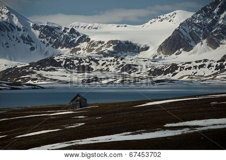 Rickety hut in fjord with mountains behind