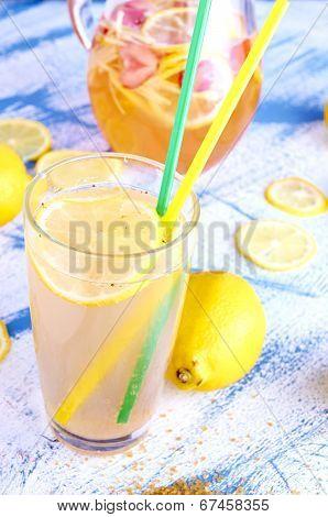Ginger lemonade in glass with pithcer on back.