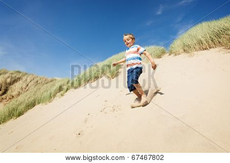 Boy running and jumping down sand dunes on a beach smiling and having fun