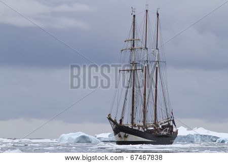 Small Sailing Ship In Antarctic Waters Between Ice Floes And Icebergs