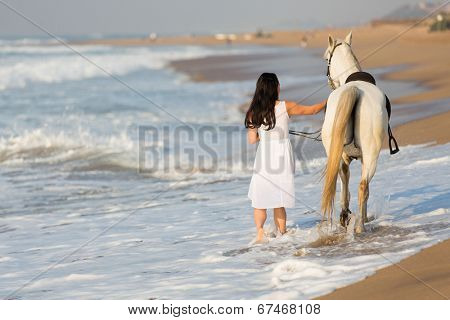 rear view of young woman walking a white horse on beach