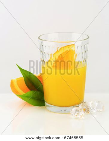 glass of citrus juice with immersed piece of fresh orange