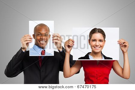Man holding a portrait of another smiling person