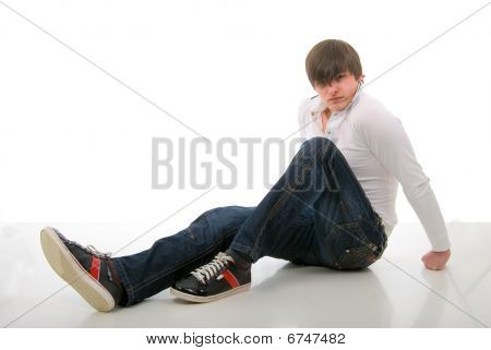Sitting Man On A Mirror Floor. Studio Shoot Over White Background.