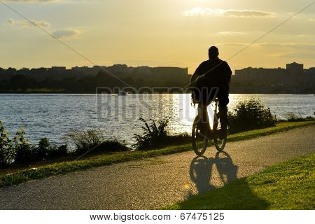 silhouette of a man cyclist riding a road bike on riverside trail