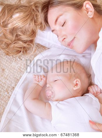 Photo of adorable newborn baby with beautiful young mother resting at home, bedtime, happy loving family, new life concept