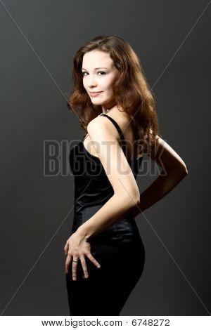caucasian dark hair girl turned backwards in black dress isolated over gray