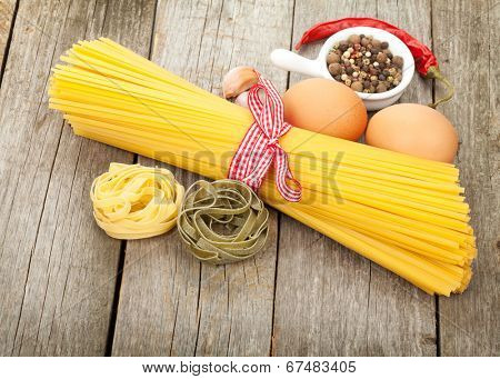 Pasta, eggs and spices on wooden table background