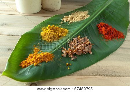 Nutmeg, curry, paprika, pepper and curcuma spices on a green banana leaf