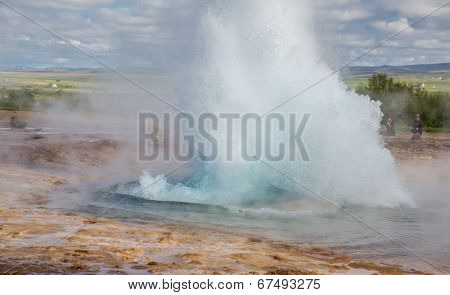 Geyser and blurred tourists