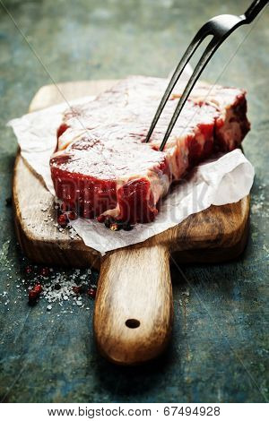 Raw beef steak with meat fork on a an old wooden table