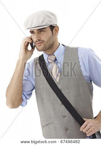 Young man talking on mobilephone, holding shoulder bag, wearing hat.
