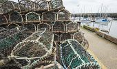 picture of lobster boat  - Commercial lobster fishing pots stacked on quayside of a fishing port - JPG