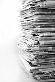 stock photo of piles  - Pile of newspapers on plain background - JPG
