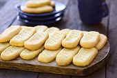 picture of shortbread  - Homebaked shortbread biscuits on wooden board with plates and cup of tea in the back  - JPG