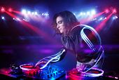 picture of disc jockey  - Pretty young disc jockey girl playing music with light beam effects on stage - JPG