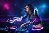 foto of disc jockey  - Beautiful disc jockey playing music with electro light effects and lights - JPG
