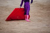 stock photo of bullfighting  - A barefoot bullfighter waits the bull with the capote during a bullfight - JPG