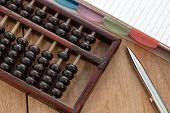 image of subtraction  - Accounting abacus on wooden table with paper and pen - JPG