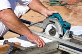 stock photo of soffit  - Construction worker uses a electric powered circular saw to cut soffit for a home being built - JPG