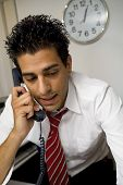 stock photo of people talking phone  - young businessman talking on the phone in his office - JPG