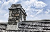 stock photo of shingles  - Historic chimney made of cobblestone sits on roof with wooden shingles - JPG
