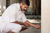stock photo of muslim man  - Muslim Man Preparing To Take Ablution In Mosque - JPG