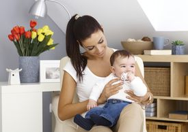 stock photo of teats  - Young mother sitting in armchair at home - JPG