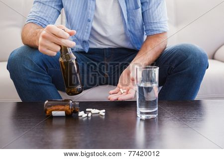 Close up of man showing pills and holding bottle in the living room