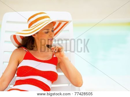 Portrait Of Relaxed Young Woman Laying On Chaise-longue