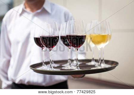 waiter with glasses with wine on the tray