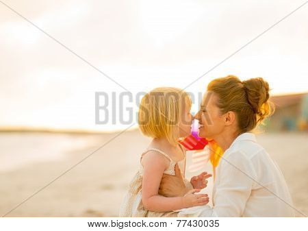 Happy Mother And Baby Girl On Beach At The Evening