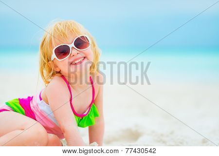 Portrait Of Happy Baby Girl In Sunglasses On Beach
